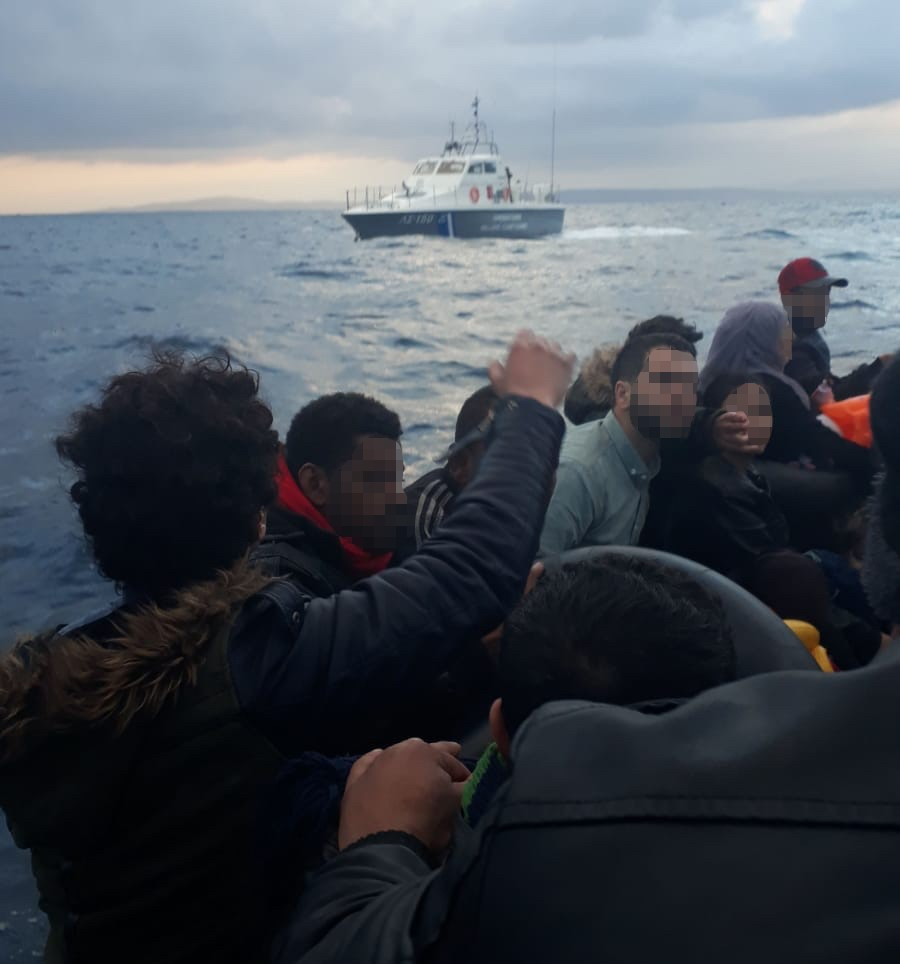 Group on a boat refouled to Turkey and Greek coast guard boat in the background